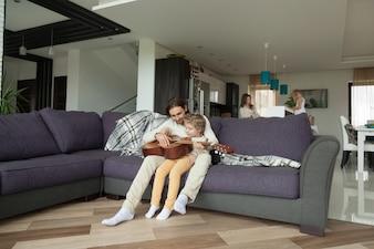 父は息子にギターを弾く娘、台所で母を助ける娘