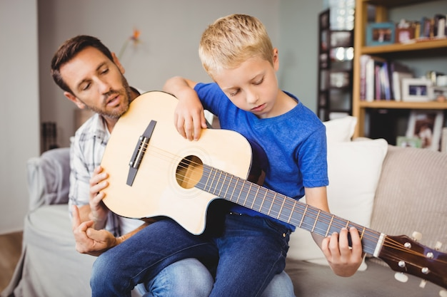 Father teaching son to play guitar while sitting on sofa