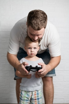 Father teaching son to play with joystick