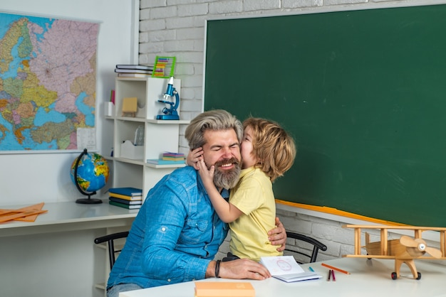 Father teaching son teachers day home school for pupil happy father and son tutoring agency elementa...