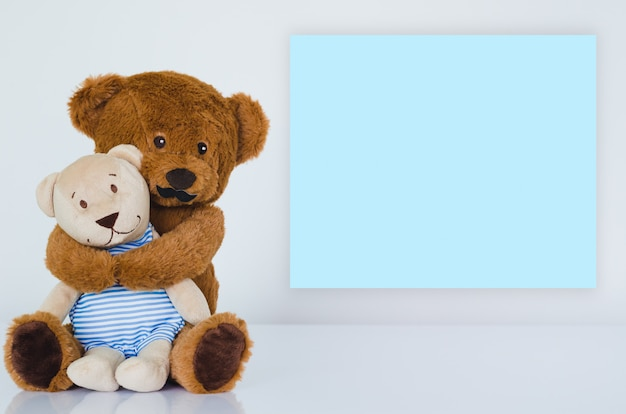 Father teddy bear with mustache hugging his son with empty blue note