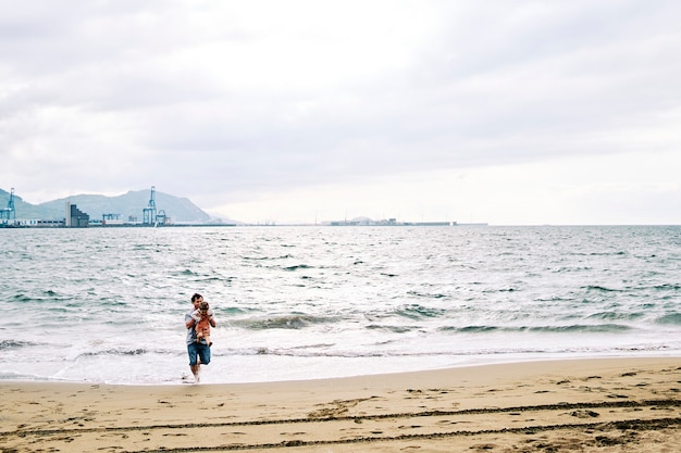 Father and three-year-old son playing on the seashore on a cloudy day at the beach