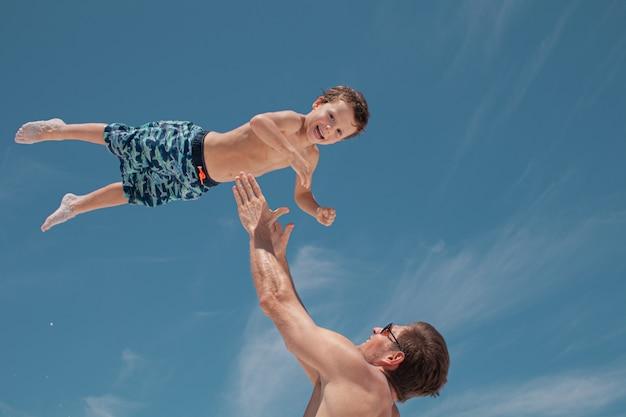 父は子供を空中に投げます。幸せな子供時代。コンセプト幸せな家族。