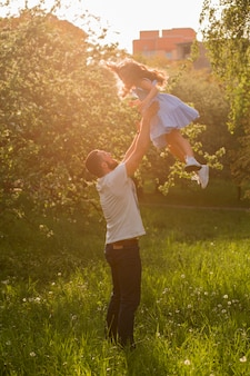 Father throwing his daughter in the air on sunny day