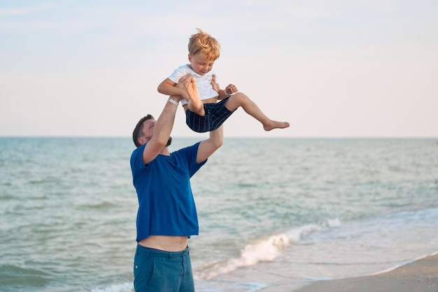父の日一緒に海の休暇を過ごす息子を投げる父の日。子供が1人いる家族。パパとの幸せな子供時代。