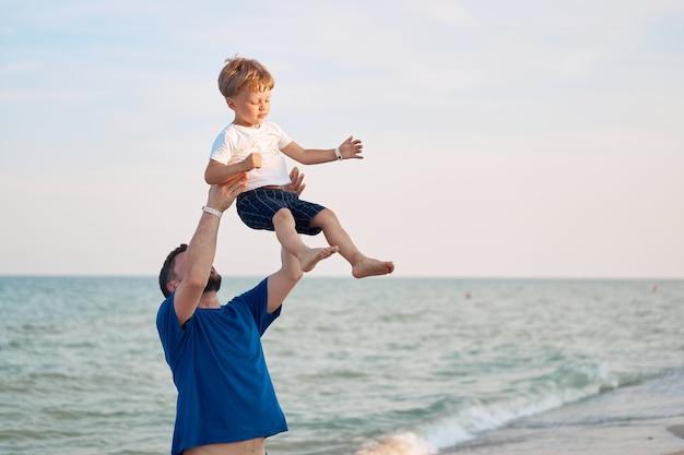 함께 시간을 보내고 아들을 던지는 아버지 바다 휴가 젊은 아빠 자식 해변 산책하는 어린 소년 아버지 날입니다. 자녀가 한 명인 가족. 아빠와 함께 행복한 어린 시절.