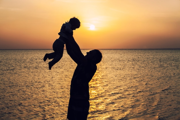 Father throwing young child silhouette on a background of dawn and morning sea