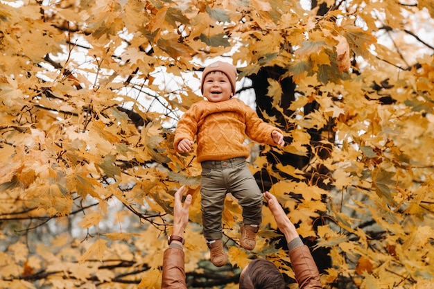 A father throws a child against the background of autumn leaves in the park. dad throws up his son on the autumn leaves.