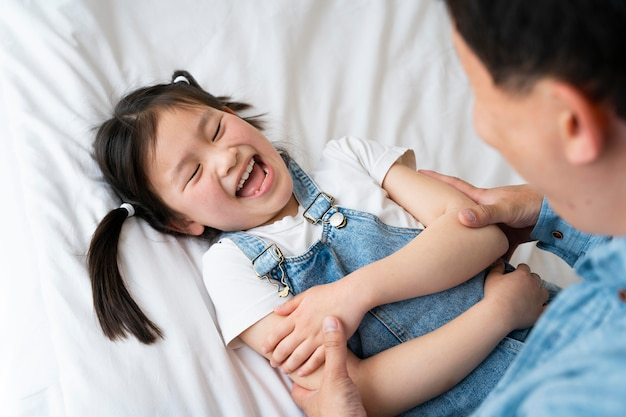 Father tickling girl close up