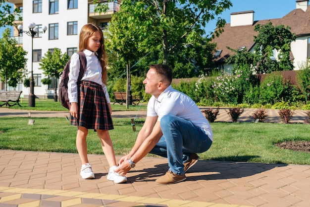 Father ties shoelaces his daughter in the street before going to school