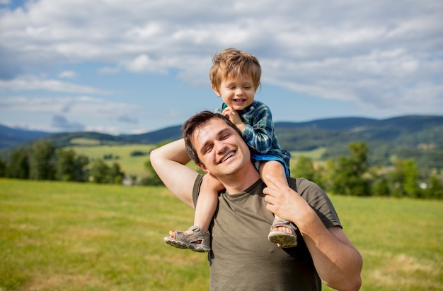 Father and toddler boy have a fun in a mountains