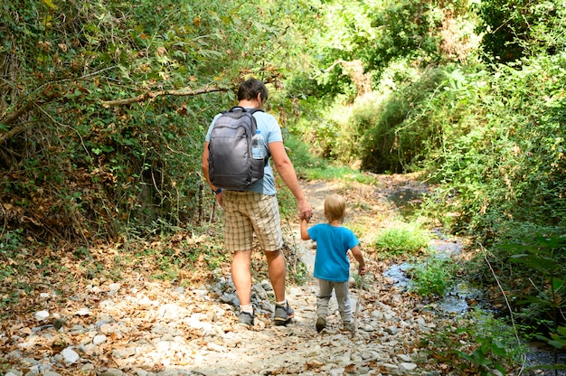 Father together his kid son and family on a hike through a mountain gorge overcomes obstacles. vacation in the new normal.