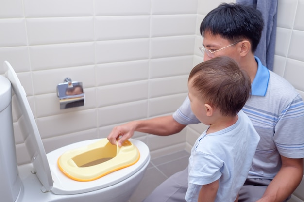 Father training sleepy son to use toilet in bathroom, asian toddler boy sitting on toilet with kid bathroom accessory