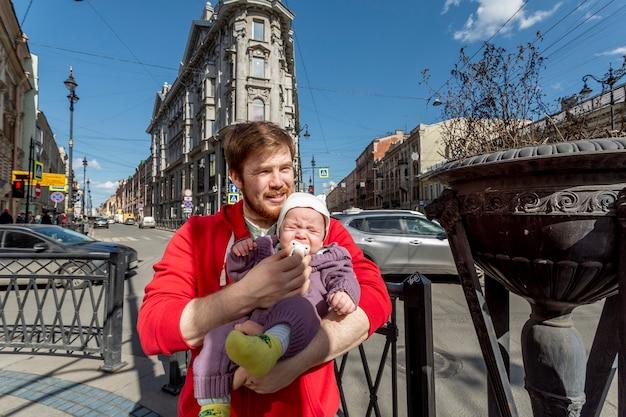 サンクトペテルブルクロシアの通りで彼の泣いている幼い息子を落ち着かせようとしている父