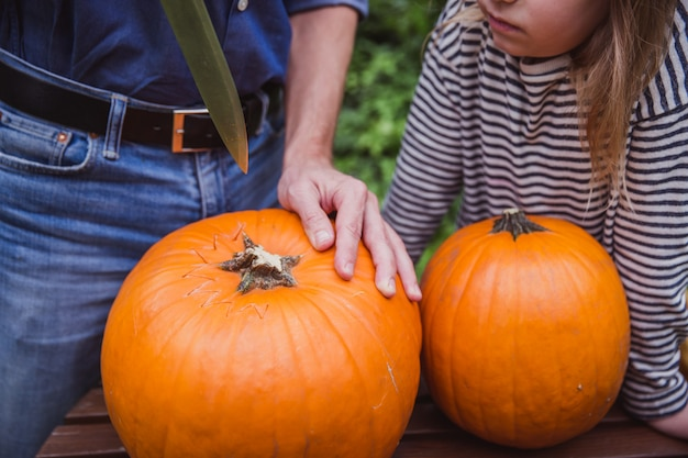 Father and two daughter carving pumpkin for halloween