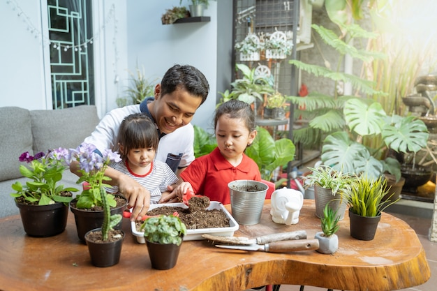 Father and two daughters are happy when using a shovel to grow potted plants