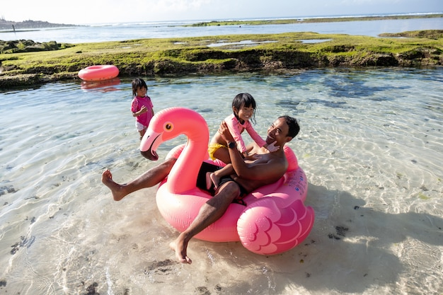 Father and two daughters ride flamingo buoy on the beach