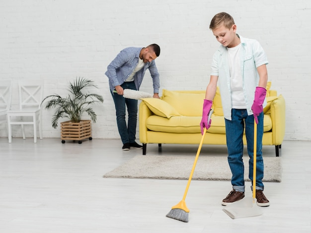 Father using duster while son uses broom