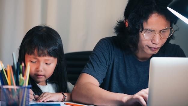 ラップトップを使用して父親は残業し、娘は夜の家のオフィスの作業テーブルで学校の宿題をやっています。