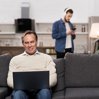 Father using laptop while son is using phone