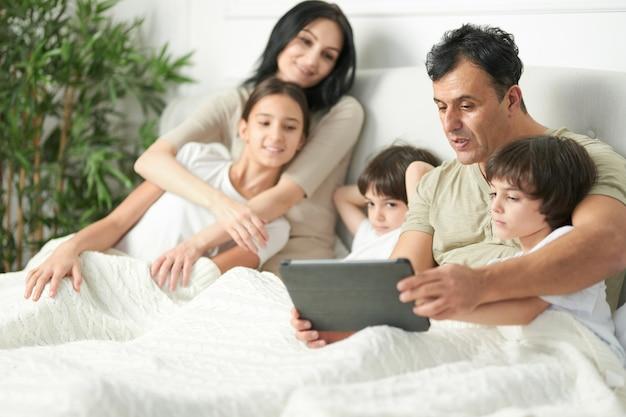 아버지는 태블릿 pc를 사용하고, 만화를 보고, 어린 두 아들과 게임을 합니다. 아침에 함께 침대에 머물고 있는 아이들과 함께 행복한 라틴 가족. 어린 시절, 아침 개념