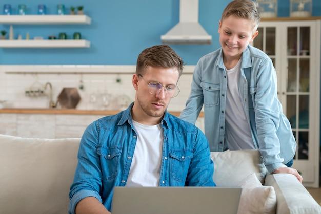 Отец, используя ноутбук и сын смотрит