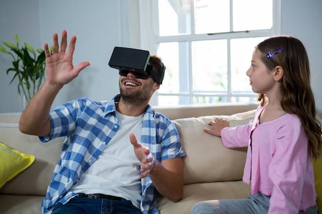 父親が仮想現実のヘッドセットを使用して、リビングルームで彼の隣に座っている娘