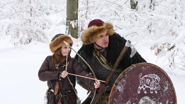 Отец викинг учил сына стрельбе из лука в зимнем лесу