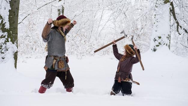 Отец викинг учит сына драке, держа в руках топор