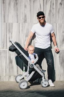 Отец гуляет с коляской и младенцем по улицам города