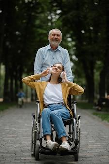 Отец ходит с дочерью-инвалидом в инвалидной коляске