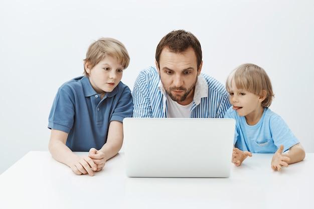 Отец смотрит мультики с сыновьями. портрет увлеченного привлекательного отца с маленькими мальчиками, сидящими за столом и с интересом и любопытством смотрящими на экран ноутбука