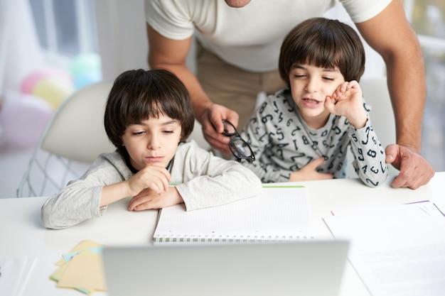 子供のためのオンラインレッスン中に彼の子供を見ている父。自宅のテーブルに一緒に座っている小さなラテン系の男の子。セレクティブフォーカス