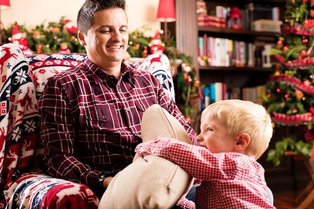 Padre guardando suo figlio a giocare con un cuscino
