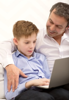 Father watching son working with laptop