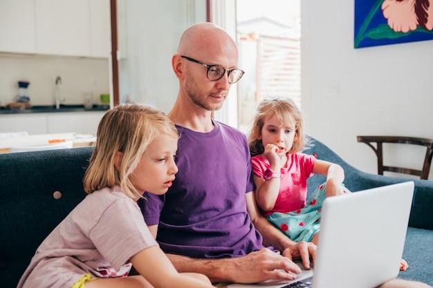 아버지는 집에서 두 딸과 함께 컴퓨터에서 스트리밍 만화를보고