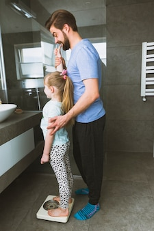 Father weighing daughter in bathroom