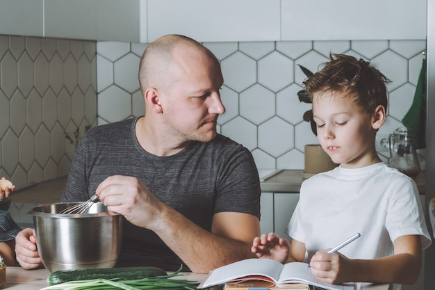 아버지는 오믈렛을 채찍질하고 아들이 집안일을하는 부엌에서 숙제를하도록 도와줍니다.