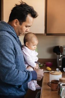 朝、両親と家族の概念でコーヒーを作るキッチンで女の赤ちゃんを持つ父親