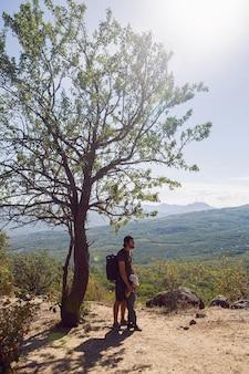 クリミア半島の夏、バックパックを背負った父と息子が山の木の隣に立っている