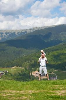 그의 어깨에 작은 아들과 아버지. 배경에 산입니다. 여름 화창한 날.