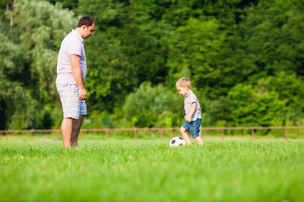 小さな息子を持つ父は緑の芝生でサッカーをします