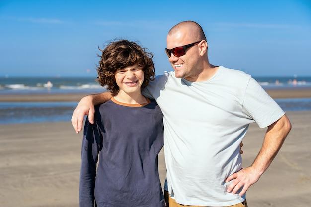 Отец с улыбающимся сыном-подростком, проводя время вместе на берегу моря. счастливый мальчик с зубными скобами.