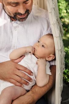 ハンモックで男の子の父親は、優しくて優しい父性を満たしています。お父さんの膝の上にかわいい息子