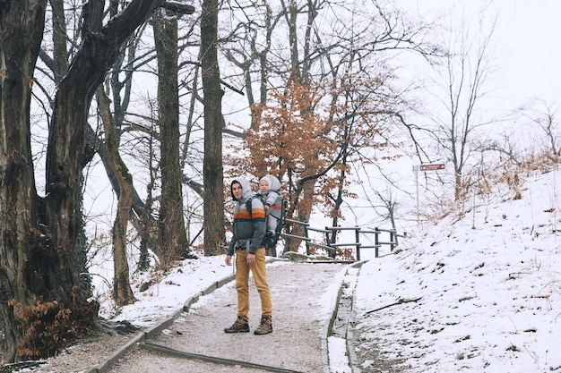Father with baby child in carrier backpack on the road to the castle of ljubljana