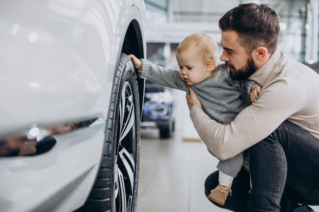 Father with baby daughter in a car showroom