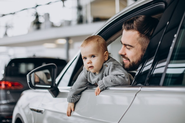 Father with baby daughter sitting in car