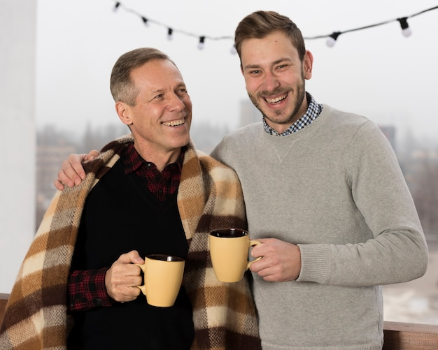Father with blanket posing with son while holding cups in hands