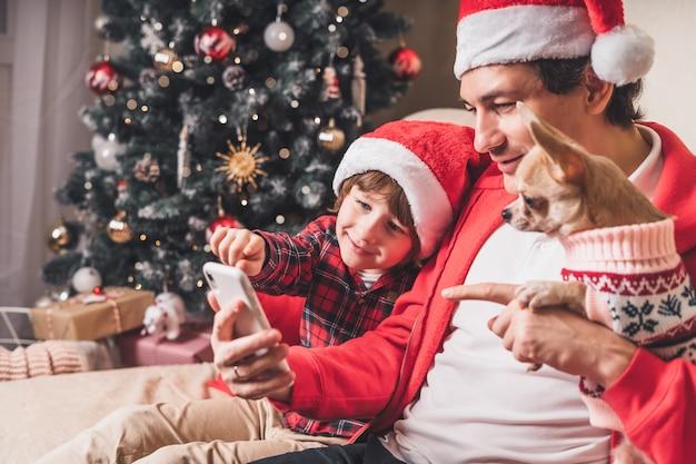 スマートフォンで子供と子犬のクリスマスの日を持つ父