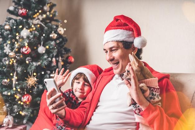 Отец с ребенком и щенок в шляпах санта-клауса, имеющих видео-чат